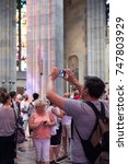 Small photo of Prague, Czech Republic - 17 August 2017: Tourists taking photographs inside St Vitus Cathedral. Man takes a photo with with mobile phone inside St Vitus Cathedral.