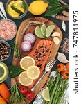 Small photo of Food to maintain a healthy heart with fresh salmon fish, vegetables, fruit, herbs, seasoning and olive oil on an olive wood board. High in omega 3 fatty acids.