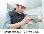electrician installing socket... | Shutterstock . vector #747952231