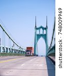 Small photo of White big rig semi truck tractor with roof aerodynamic spoiler and without semi trailer driving by awesome gothic metal arched St Johns bridge with towers and another cars of bridge traffic