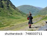 a scotsman playing bagpipes in... | Shutterstock . vector #748033711