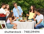 young friends having barbecue... | Shutterstock . vector #748139494
