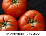 Close-up of freshly washed, sunlit tomatoes on a black woven placemat - stock photo