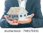 business man holding an house... | Shutterstock . vector #748170331
