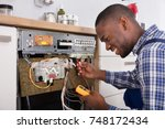 young male african technician... | Shutterstock . vector #748172434