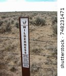 Small photo of Bloomfield, New Mexico, USA - July 26, 2016: Wilderness boundary marker posted by the U.S. Bureau of Land Management indicates the start of the De-Na-Zin Wilderness near Chaco Canyon.