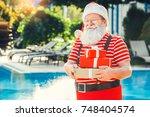 santa claus near the pool...   Shutterstock . vector #748404574