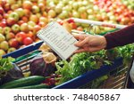 person shopping at the grocery... | Shutterstock . vector #748405867