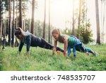 two female friends doing push... | Shutterstock . vector #748535707