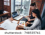 young women working on a new... | Shutterstock . vector #748535761