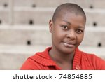 Headshot of a young black woman with a shaved head - stock photo
