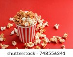 cup with tasty caramel popcorn... | Shutterstock . vector #748556341