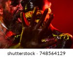 Small photo of Halloween couple with stop hand gesture on red background. Man with bloody beard lick woman skull makeup. Prohibition, denial, rejection concept.