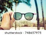 the girl is holding sunglasses... | Shutterstock . vector #748657975