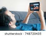 man watching tv series on... | Shutterstock . vector #748720435