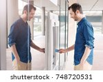 man using his credit card in an ... | Shutterstock . vector #748720531