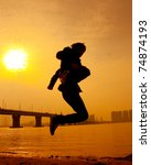 Silhouette of athletic men to the sea at sunset. Give me the power. - stock photo