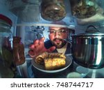 hungry young man takes plate... | Shutterstock . vector #748744717