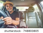 asian man driving car and look... | Shutterstock . vector #748803805