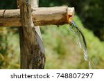 Natural water source. Natural spring of water. Clean, fresh, natural spring of drinking water falls from a wooden channel