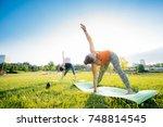 girls perform yoga exercises in ... | Shutterstock . vector #748814545