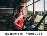 sport girl run orbitrek gym... | Shutterstock . vector #748863265