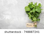 fresh mint leafs on grey wooden ... | Shutterstock . vector #748887241