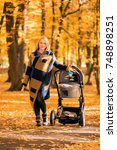 a young mother with a stroller... | Shutterstock . vector #748898251