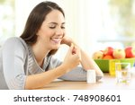 happy woman taking omega 3... | Shutterstock . vector #748908601