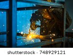 the worker in overalls and a... | Shutterstock . vector #748929121