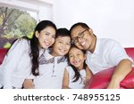 happy parents sitting on the... | Shutterstock . vector #748955125