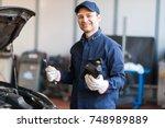 portrait of an auto mechanic... | Shutterstock . vector #748989889