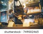 black man works in pastry shop.   Shutterstock . vector #749002465