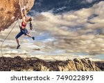 Stock photo female climber struggling up a sheer cliff 749022895