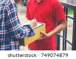 young man delivering package to ... | Shutterstock . vector #749074879