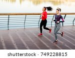 two young women running by... | Shutterstock . vector #749228815
