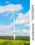 Small photo of Alternative energy source. Turbine on field on cloudy blue sky. Global warming, climate change. Eco power, green technology concept. Wind farm in Lower Saxony, Germany.