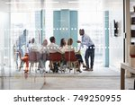 young male boss stands leaning...   Shutterstock . vector #749250955