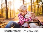 Stock photo senior woman with dog on a walk in an autumn forest 749267251