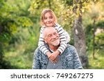 grandfather carrying his... | Shutterstock . vector #749267275