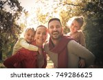 parents carrying daughters on... | Shutterstock . vector #749286625