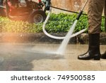 worker cleaning driveway with... | Shutterstock . vector #749500585