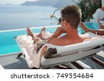 young man by the swimming pool... | Shutterstock . vector #749554684