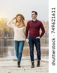Small photo of Enjoying carefree walk. Full-length of beautiful young couple walking outdoors. Gorgeous woman and handsome man looking away and smiling while having fun outdoors.