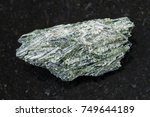 Small photo of macro shooting of natural mineral rock specimen - rough Actinolite stone on dark granite background from Verkhny Ufaley district, Ural, Russia