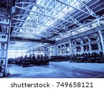 Small photo of Unified standard typical span prefabricated of a reinforced concrete frame production building. Industrial metalwork production hall. Background in blue tone.