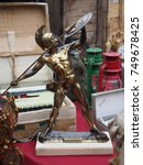 Small photo of Ferrara, Italy - November 4, 2017. Flea market in the main square. Small metal statue depicting Achilles.