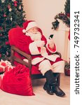 Small photo of Holly jolly x mas, noel is soon! Concentrated pensive santa think, study list of children's wishes and gifts on pda, ready to make dreams come true, bring happiness to kids