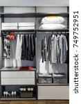 Small photo of modern wooden wardrobe with clothes hanging on rail in walk in closet design interior