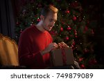 man tying bow on christmas gift | Shutterstock . vector #749879089